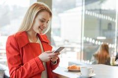 Nette blonde Mädchenmitteilung am Telefon im Café Stockfoto
