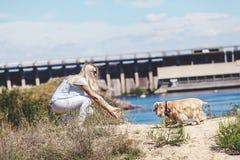 Nette blonde Mädchenspiele mit Cocker spaniel Lizenzfreies Stockfoto