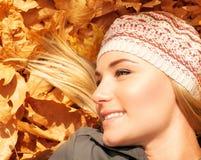 Nette blonde Niederlegung auf Baumblättern Stockfotografie