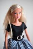Nette blonde Puppe im karierten blauen und weißen Rock Lizenzfreie Stockfotos