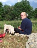 Nette blonde reife Frau mit Pughundedem stillstehen Stockbilder