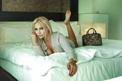 Nette blonde Schönheit, die im Großen Bett sich entspannt. Lizenzfreie Stockfotos