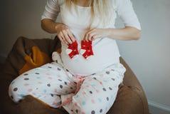 Nette blonde schwangere Frau in beschmutzten Pyjamas sitzt auf dem Bohnentaschenstuhl Sie hält kleine rote Socken nahe ihrem Bauc stockfotografie
