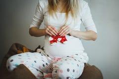 Nette blonde schwangere Frau in beschmutzten Pyjamas sitzt auf dem Bohnentaschenstuhl Sie h?lt kleine rote Socken nahe ihrem Bauc lizenzfreies stockfoto
