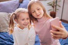 Nette blonde Schwestern, die Fotos an ihrem Telefon machen Lizenzfreie Stockfotos