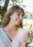 Nette blonde sitzende Außenseite, die mit Champagner röstet Lizenzfreie Stockfotografie