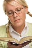 Nette blonde Spiele mit Pferdeschwänzen u. liest ein Buch Stockfotos