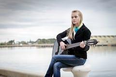 Nette blonde spielende Gitarre beim Sitzen auf dem bitt Lizenzfreies Stockfoto