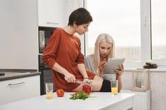 Nette blonde Tablette der Mädchenlesezufuhr herein mit ihrer Freundin, während sie Gemüse schneidet, Salat zubereitend Alle beide Stockfotografie