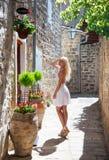 Nette blonde touristische Frau im weißen Kleid gehend entlang das kleine Lizenzfreies Stockbild