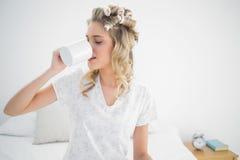 Nette blonde tragende Haarlockenwickler, die Kaffee trinken Stockbilder