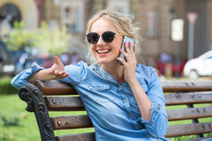 Nette blonde Unterhaltung an einem Handy Lizenzfreies Stockbild