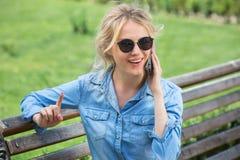 Nette blonde Unterhaltung an einem Handy Stockfotografie