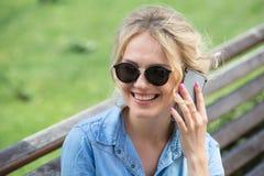 Nette blonde Unterhaltung an einem Handy Lizenzfreie Stockfotografie