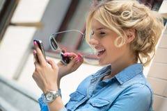 Nette blonde Unterhaltung an einem Handy Lizenzfreie Stockbilder