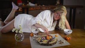Nette Blondine in den Bademantellügen auf Tabelle stock video footage