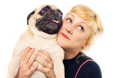 Nette Blondine, die einen Pug umarmt Stockbild