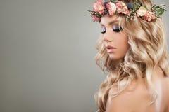 Nette Blondine mit Blumen, blonde gelockte Frisur Stockfoto