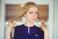 Nette Blondine mit dem umsponnenen Haarspielen, gekleidet in einem blauen Kleid, schönes Porträt im Haus, einfaches Hauptbild, Ha Lizenzfreies Stockfoto