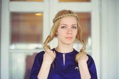 Nette Blondine mit dem umsponnenen Haarspielen, gekleidet in einem blauen Kleid, schönes Porträt im Haus, einfaches Hauptbild, Ha Stockfotografie