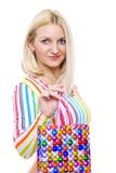 Nette Blondine mit einem Lächeln demonstriert das Paket Stockbilder
