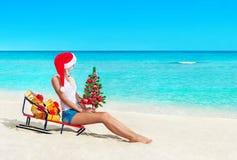 Nette Blondine am sandigen Strand des tropischen Ozeans in rotem Sankt-Hut stockfotos