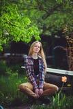 Nette Blondine sitzen in einem Hausgarten, auf einem Hintergrund von vielen grünen Bäumen und Tulpen, ein schönes Porträt einer r Lizenzfreie Stockfotos
