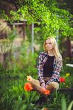 Nette Blondine sitzen in einem Hausgarten, auf einem Hintergrund von vielen grünen Bäumen und Tulpen, ein schönes Porträt einer r Lizenzfreie Stockfotografie