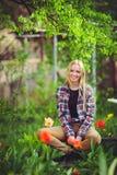 Nette Blondine sitzen in einem Hausgarten, auf einem Hintergrund von vielen grünen Bäumen und Tulpen, ein schönes Porträt einer r Stockfotos