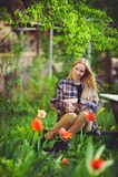 Nette Blondine sitzen in einem Hausgarten, auf einem Hintergrund von vielen grünen Bäumen und Tulpen, ein schönes Porträt einer r Stockbild