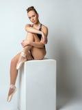 Nette braunäugige Ballerina, die das Sitzen auf Würfel aufwirft Stockfotos