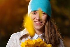 Nette braune behaarte Frau mit Herbstlaub Lizenzfreie Stockbilder