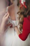 Nette Brautjungfern, die schöner sexy Braut helfen, dres an zu setzen lizenzfreies stockfoto