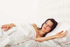Nette Brunettefrau, die im weißen Bett schläft Stockfoto