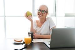 Nette Dame mit dem Apfel, der in der Küche sitzt und Kamera schaut Stockfotos