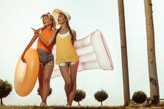 Nette Damen, die zum Strand mit aufblasbaren Wasserspielwaren vorangehen lizenzfreie stockfotos