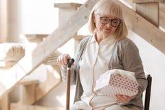 Nette deprimierte Frau, die eine Geschenkbox hält Lizenzfreie Stockbilder