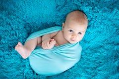 Nette drei Monate alte Baby in der blauen Verpackung, liegend auf einem blauen bla Lizenzfreie Stockfotos