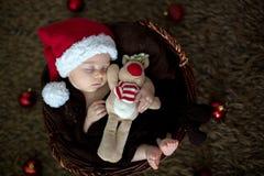 Nette drei Monate alte Baby mit Bärnhut in einem Korb, schlafend Stockfotografie