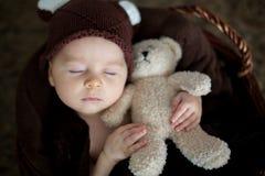 Nette drei Monate alte Baby mit Bärnhut in einem Korb, schlafend Stockbilder
