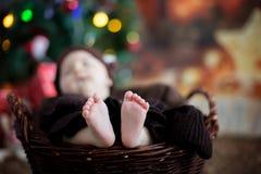 Nette drei Monate alte Baby mit Bärnhut in einem Korb, schlafend Lizenzfreies Stockbild