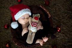 Nette drei Monate alte Baby mit Bärnhut in einem Korb, schlafend Stockfoto