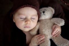 Nette drei Monate alte Baby mit Bärnhut in einem Korb, schlafend Lizenzfreie Stockfotos