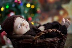 Nette drei Monate alte Baby mit Bärnhut in einem Korb, schlafend Lizenzfreie Stockfotografie
