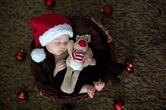 Nette drei Monate alte Baby mit Bärnhut in einem Korb, schlafend Lizenzfreies Stockfoto