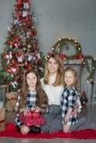 Nette ehrfürchtige blonde Muttermutter mit zwei Mädchentöchtern, die voll neues Jahr-Weihnachten nah an Weihnachtsbaum von Spielw Lizenzfreie Stockfotos