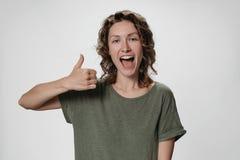Nette enthusiastische junge gelockte Frau mit öffnet die Augen und Mund, die weit darstellen stockfotos