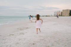 Nette entzückende glückliche junge kleine Mädchen in den hübschen Kleidern, die im Urlaub am tropischen Strand durch das Wasser a stockbilder
