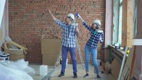 Nette Erbauer tanzen während der Reparatur stock video