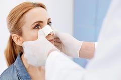 Nette ernste Frau, die Schönheitschirurgie durchmacht Lizenzfreies Stockfoto